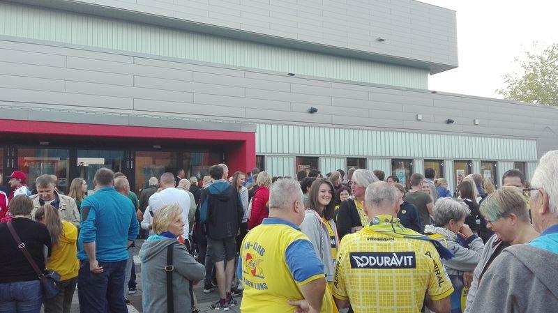 Heimfans und etliche Menschen in Löwen-Gelb warten vor der EmslandArena in Lingen (Ems).